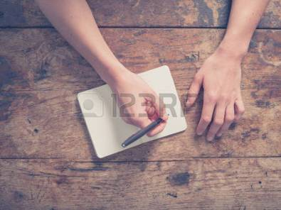 39293863-close-up-on-the-hands-of-a-young-woman-as-she-is-writing-in-a-small-notepad-at-a-wooden-table