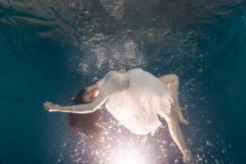 Young woman underwater floating with white dress