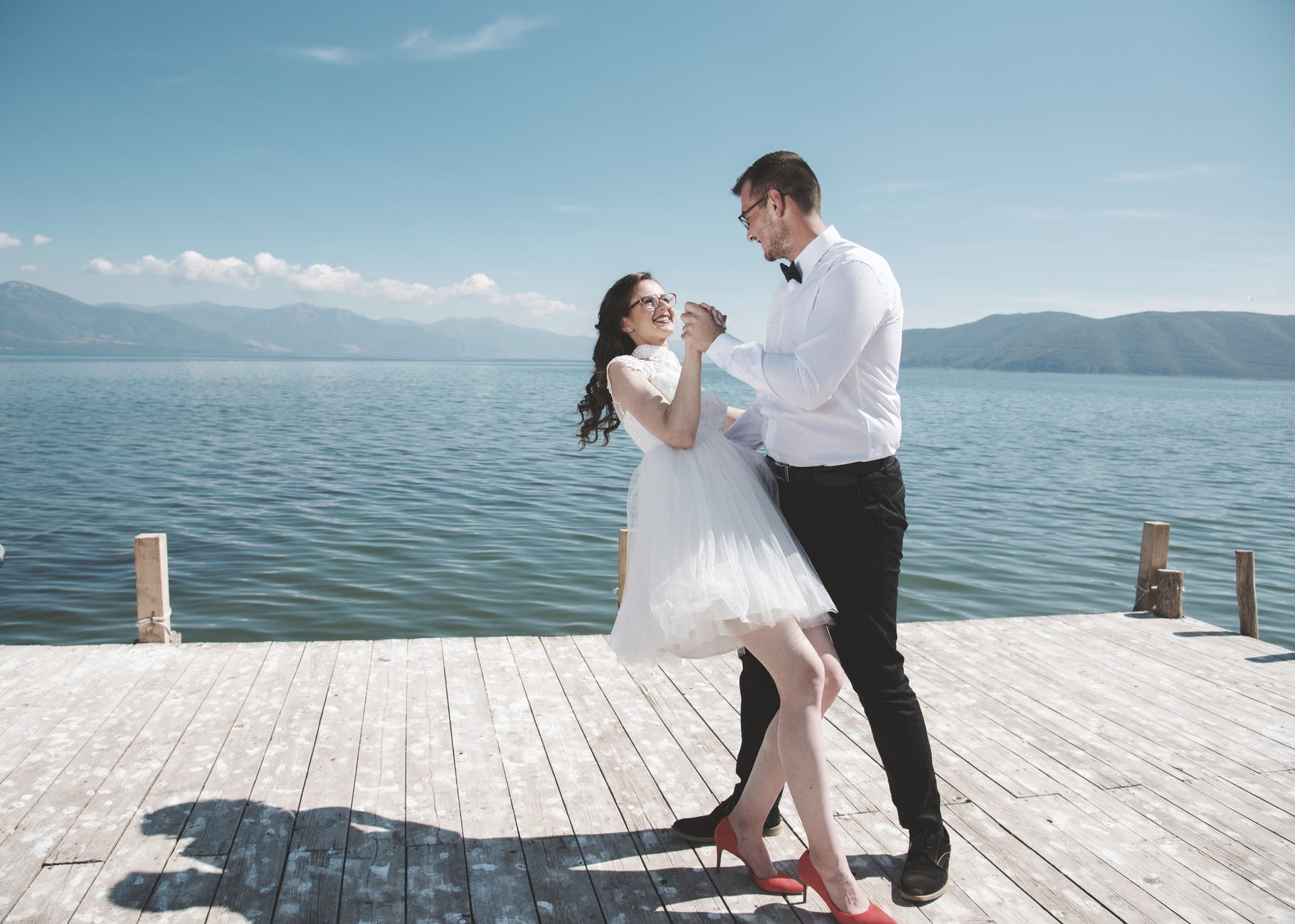man and woman dancing on dock