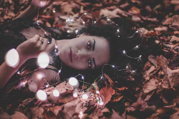 woman lying on dried leaves holding string lights