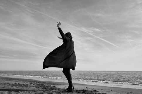 grayscale photography of woman standing on seashore