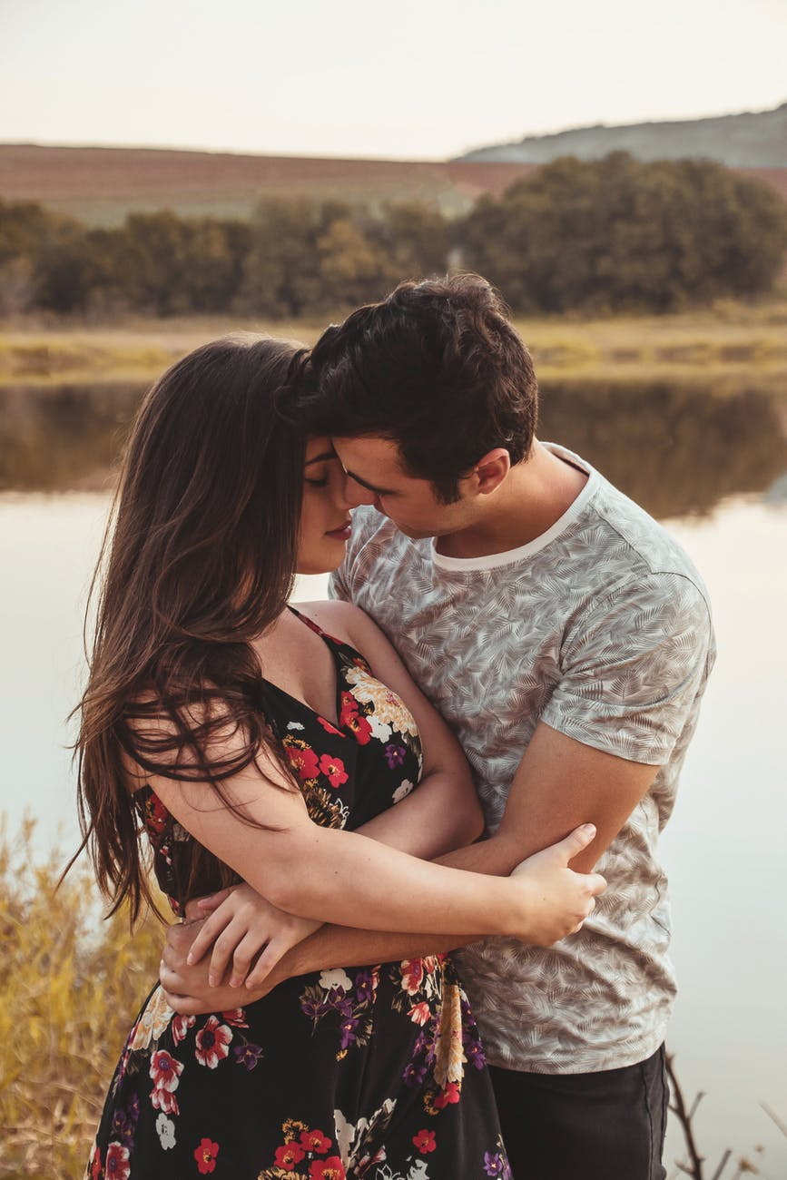 man and woman facing each other while hugging near river